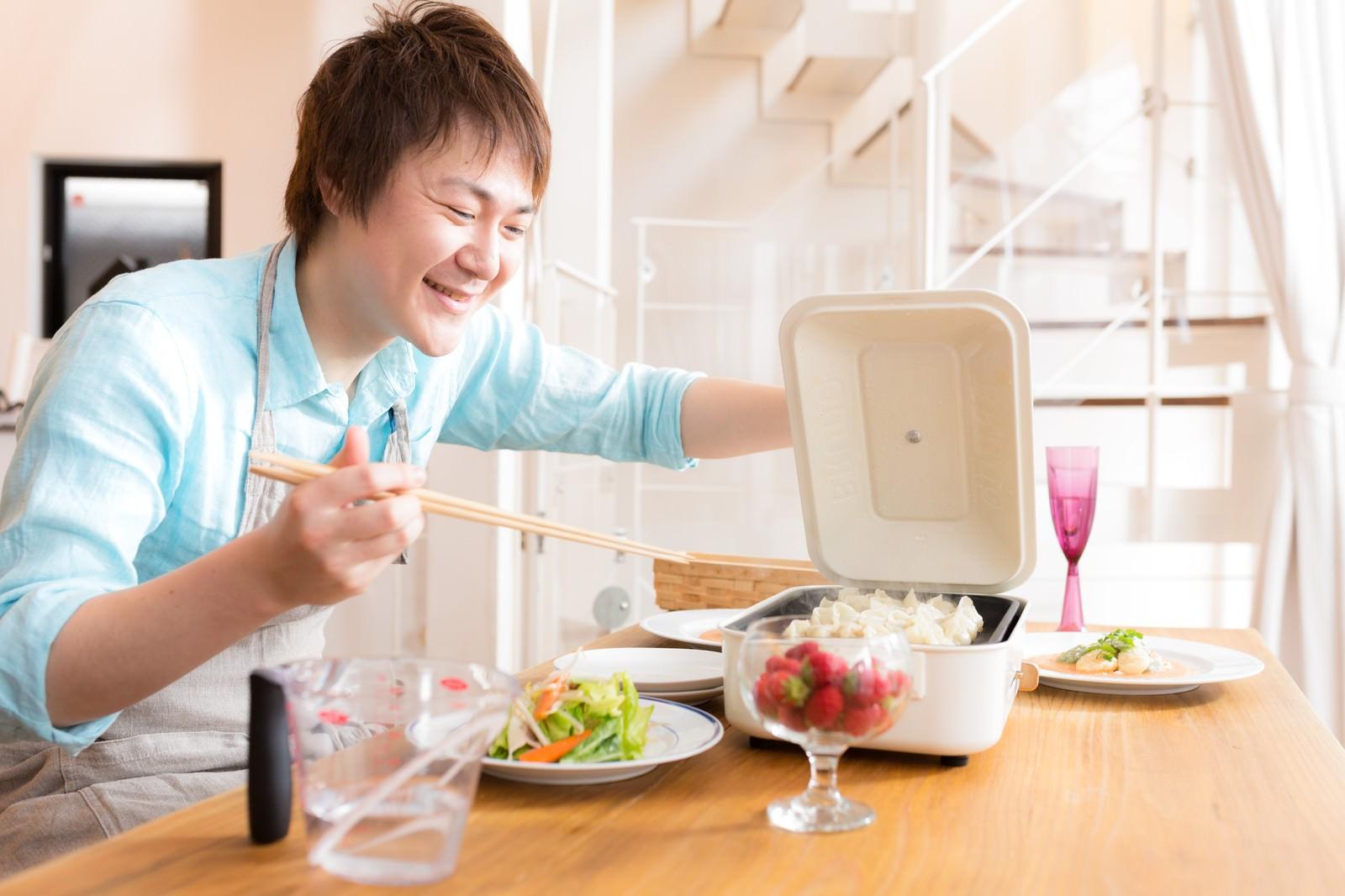 「「餃子焼けたかな?」と待ちきれない笑顔の夫」の写真[モデル:五十嵐夫妻]