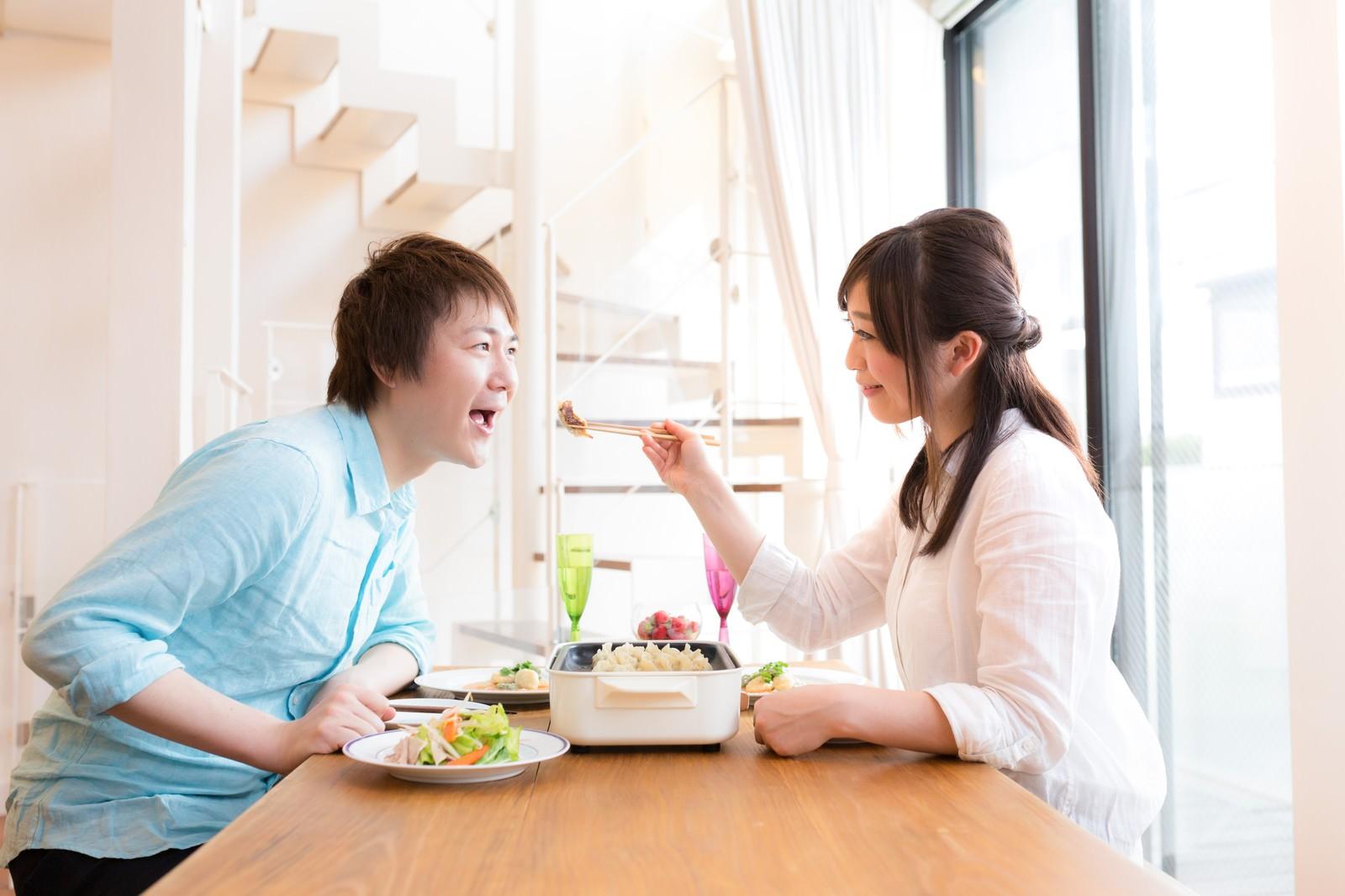 「夫を餃子で餌付けする妻と単純な夫」の写真[モデル:五十嵐夫妻]
