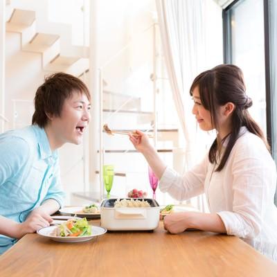 「夫を餃子で餌付けする妻と単純な夫」の写真素材