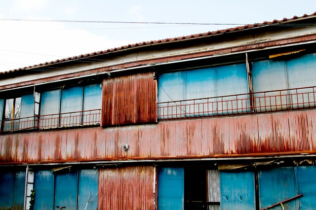 朽ちたトタンのアパートの写真