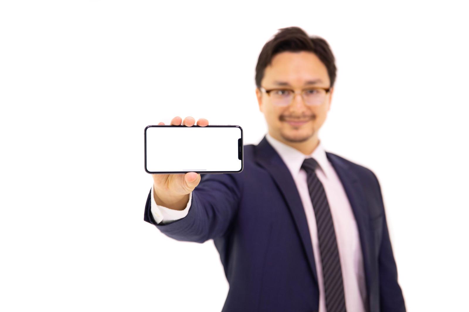 「XS MAXの大画面(6.5インチディスプレイ)を強調する外国人」の写真[モデル:Max_Ezaki]