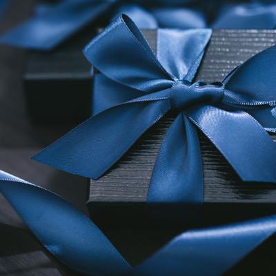 青いリボンで封がされたプレゼントの写真