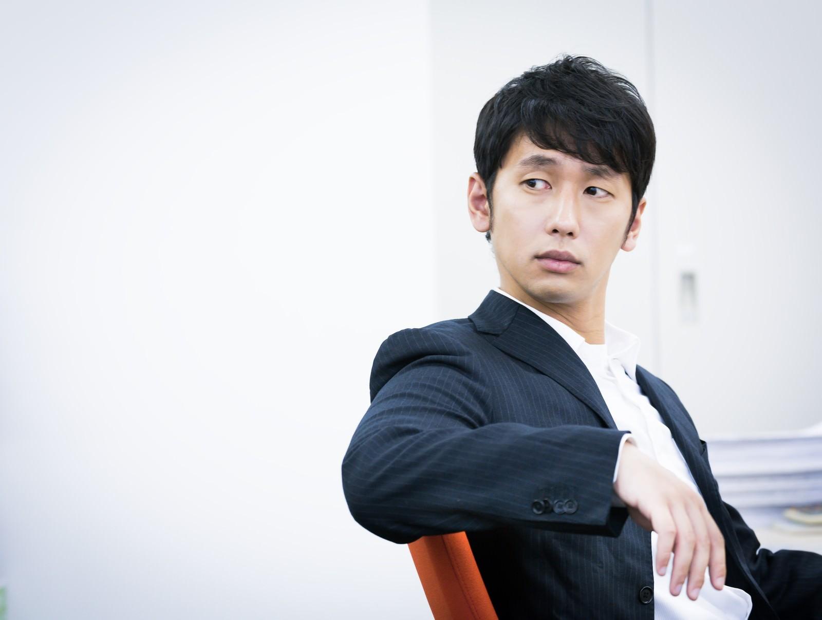 「「今日はノーネクタイたい」と言いながら振り返る九州出身の男性」の写真[モデル:大川竜弥]
