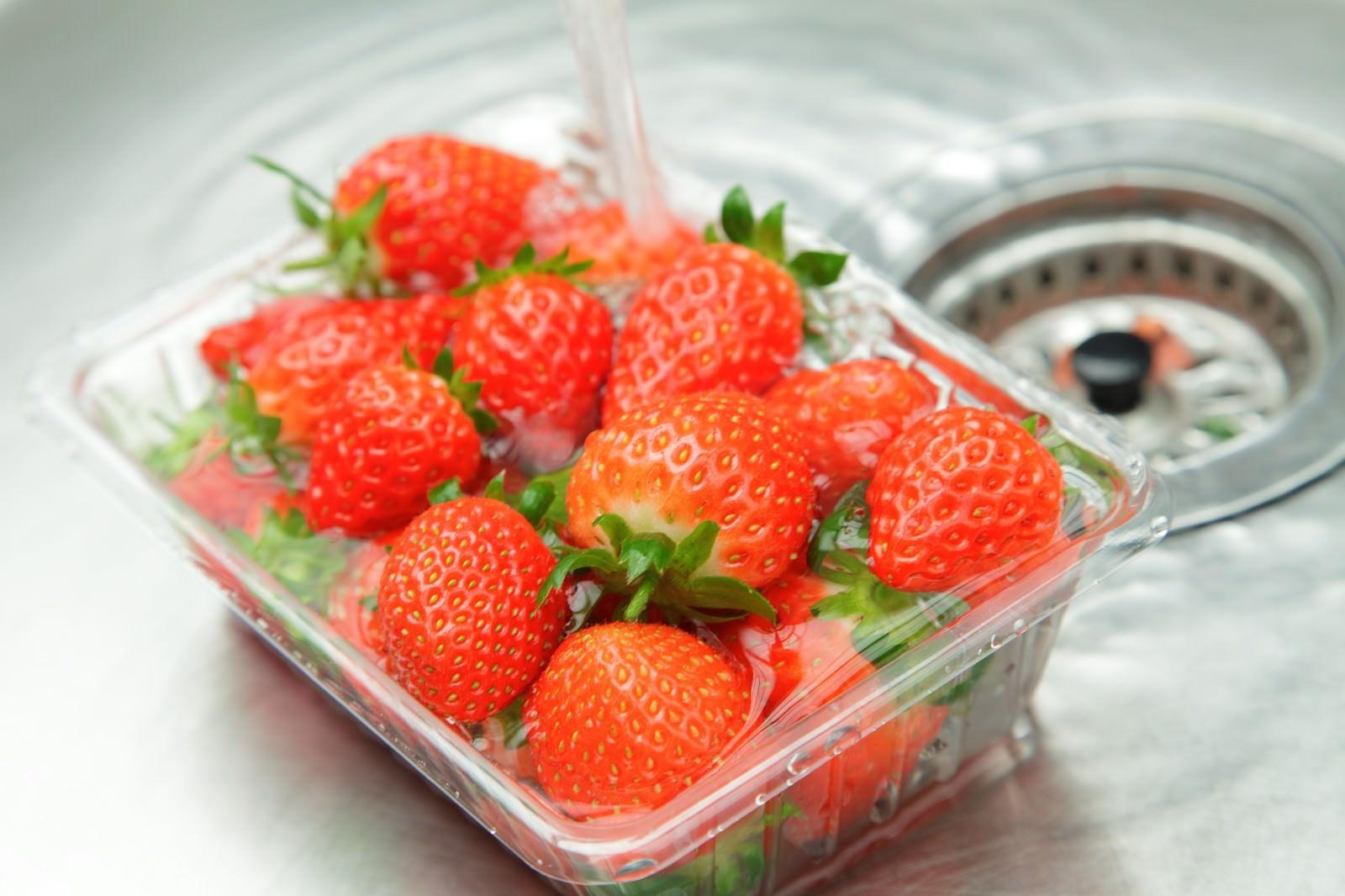 「台所でパックに入った苺に水をかける」の写真