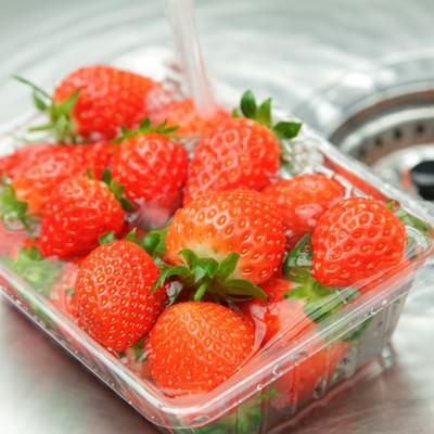 「台所でパックに入った苺に水をかける」の写真素材