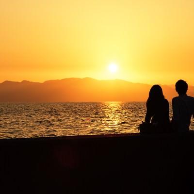 「海沿いの夕焼けとカップルのシルエット」の写真素材