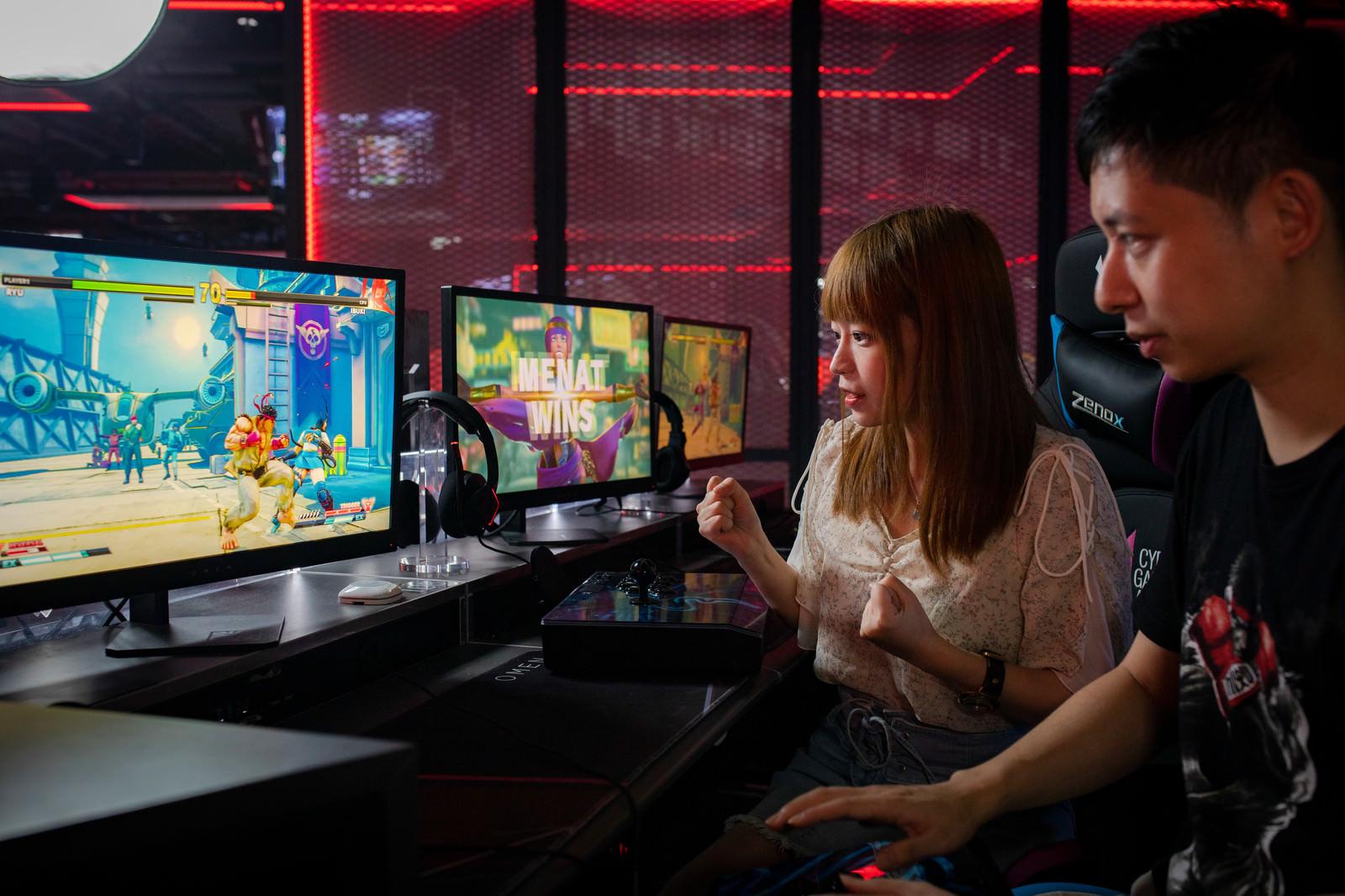 「eスポーツ施設で2D格闘ゲームをプレイする男女カップル - ストリートファイターV」の写真[モデル:Humanbomb まめち]