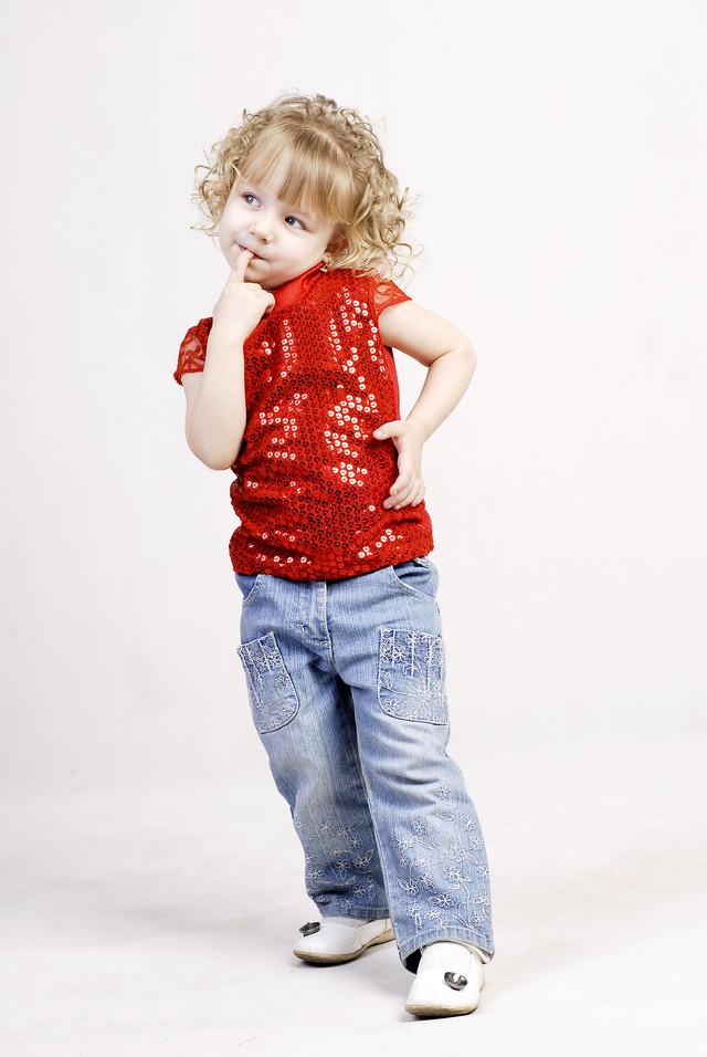 指をくわえる幼いブロンドの女の子の写真