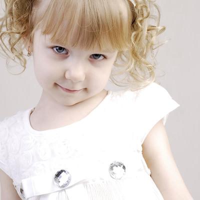 白いお洋服を着たブロンドヘアの子供の写真