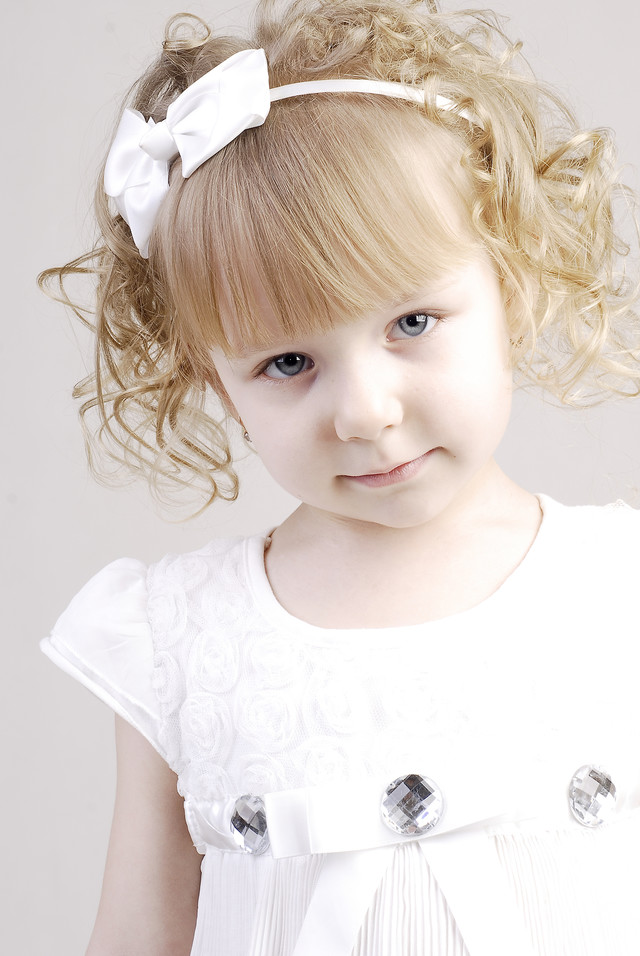 パーティ用におめかししたブロンドヘアの幼い女の子の写真