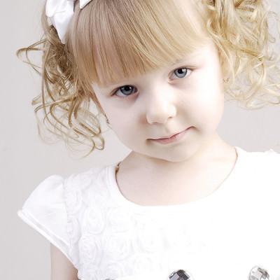 「パーティ用におめかししたブロンドヘアの幼い女の子」の写真素材
