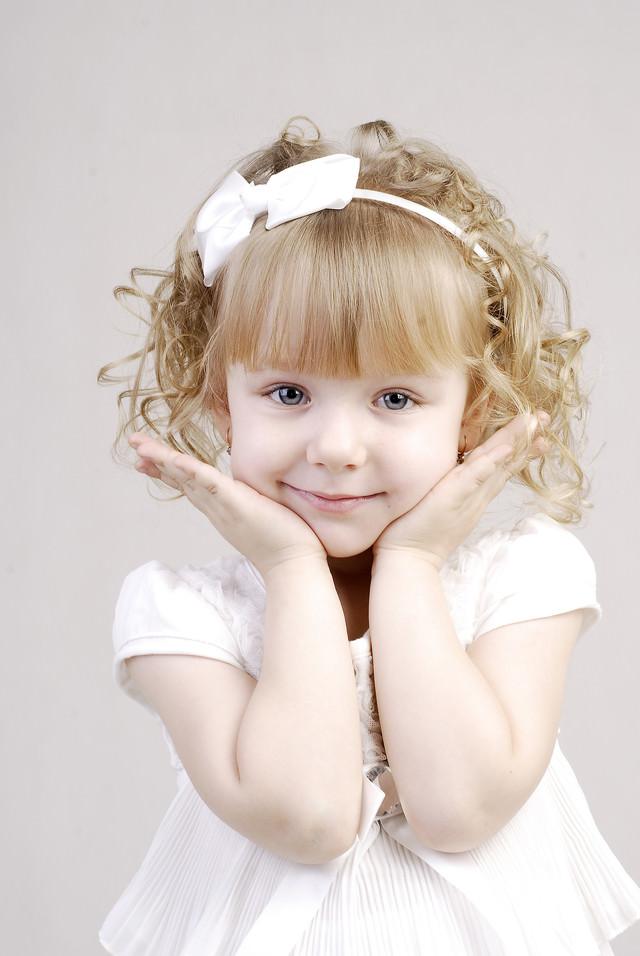 白いドレスを着て可愛さアピールをするブロンドヘアの幼い女の子の写真