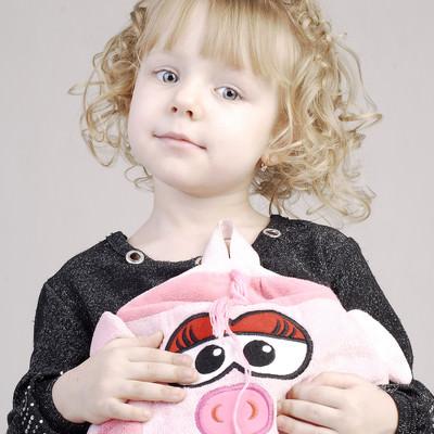 おどけた表情でぶたのバッグを持つ幼い女の子の写真