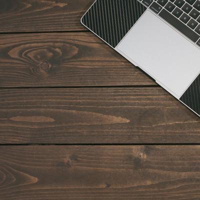 「木目のテーブルに置かれたPCとスマホ」の写真素材