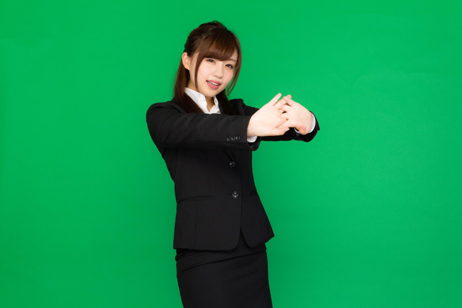 「肩こりが酷くて両手を前に出して伸びをする事務の女性(グリーンバック)」の写真[モデル:河村友歌]