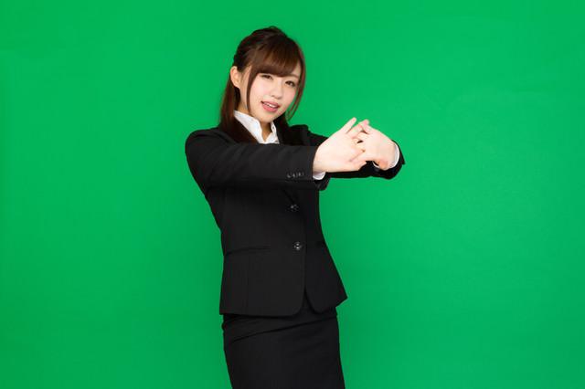 肩こりが酷くて両手を前に出して伸びをする事務の女性(グリーンバック)の写真
