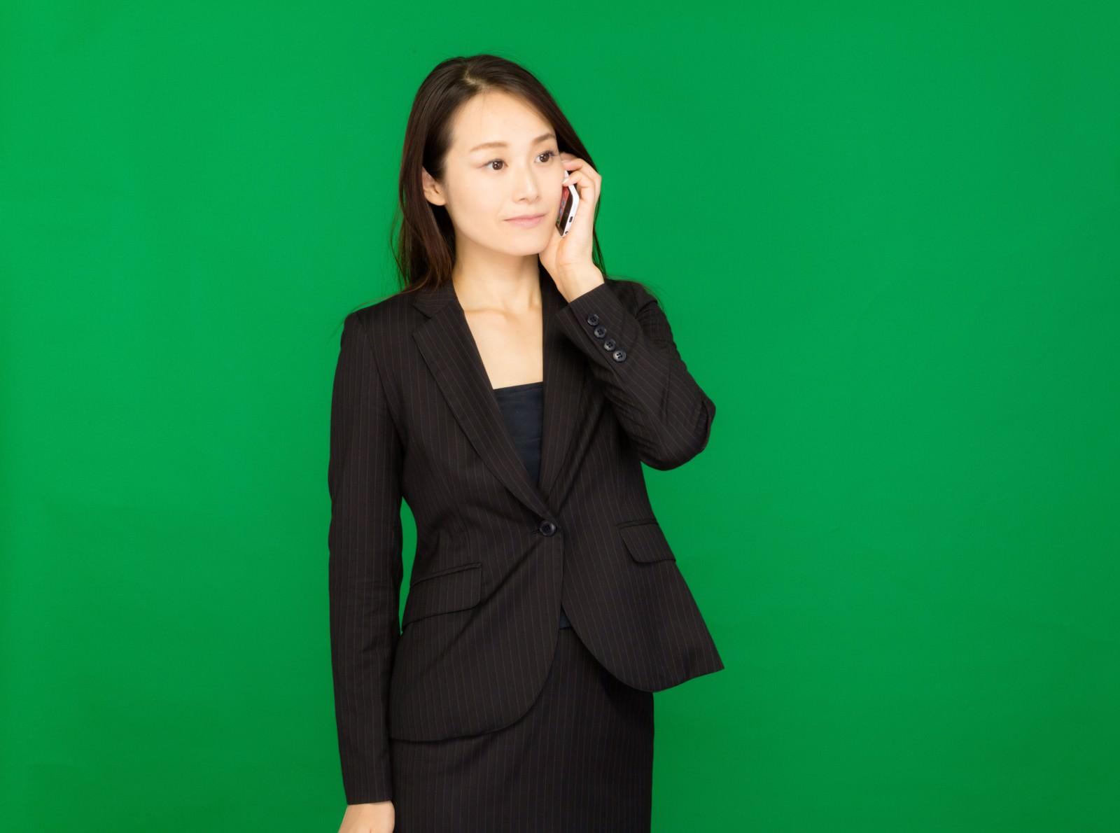 「電話で社長に確認するキャリアウーマン(グリーンバック)」の写真[モデル:土本寛子]