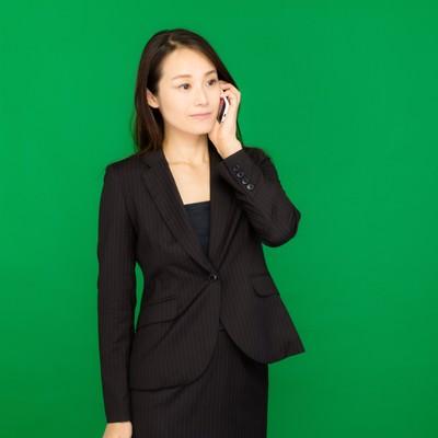 「電話で社長に確認するキャリアウーマン(グリーンバック)」の写真素材