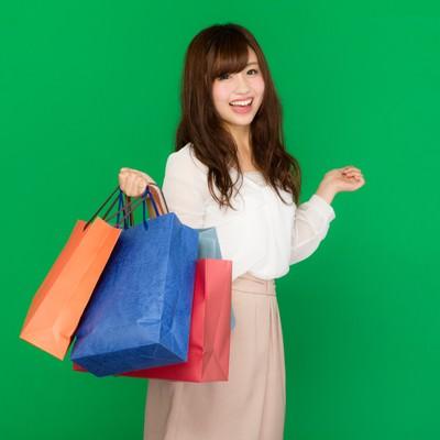 バーゲンセールでショッピングを楽しむキラキラ女子(グリーンバック)の写真