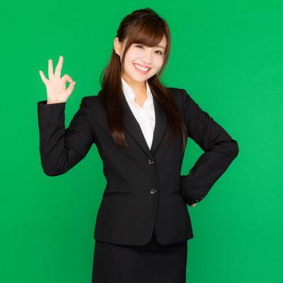 「バッチリOK!と手で合図を送るスーツ姿の若い女性(グリーンバック)」の写真素材