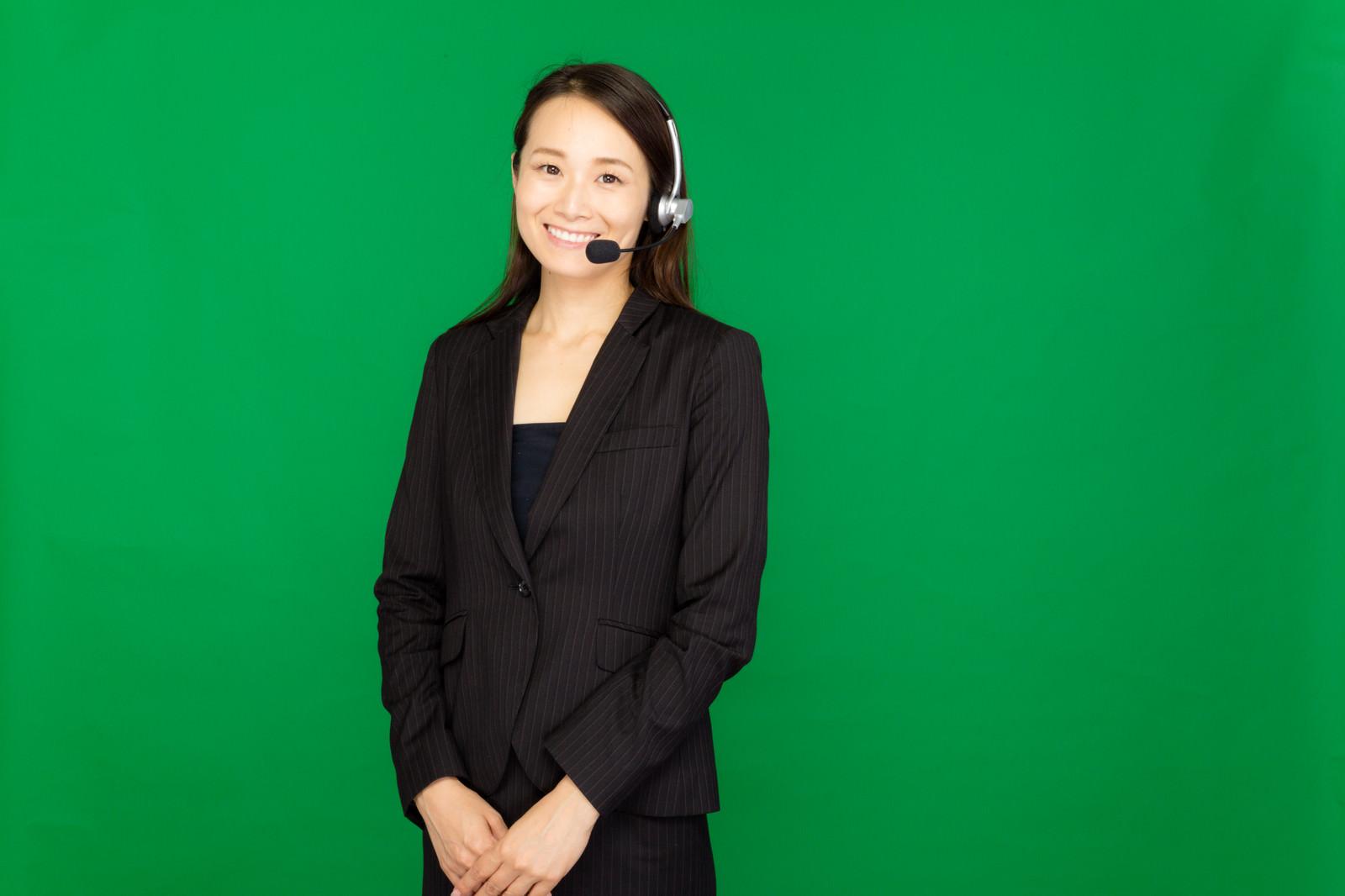 「ヘッドセットを装着したコールセンターの女性(グリーンバック)」の写真[モデル:土本寛子]