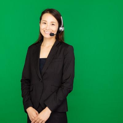 「ヘッドセットを装着したコールセンターの女性(グリーンバック)」の写真素材