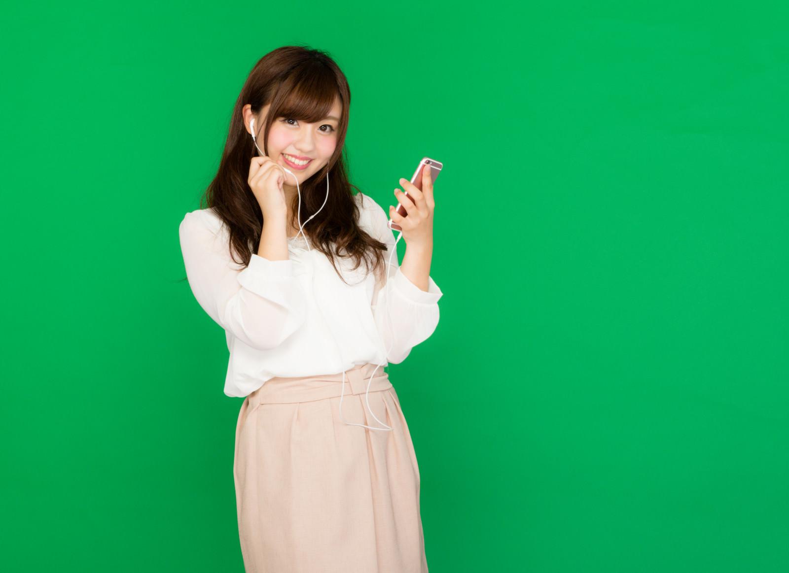 「イヤホンマイクで通話する女性(グリーンバック)」の写真[モデル:河村友歌]