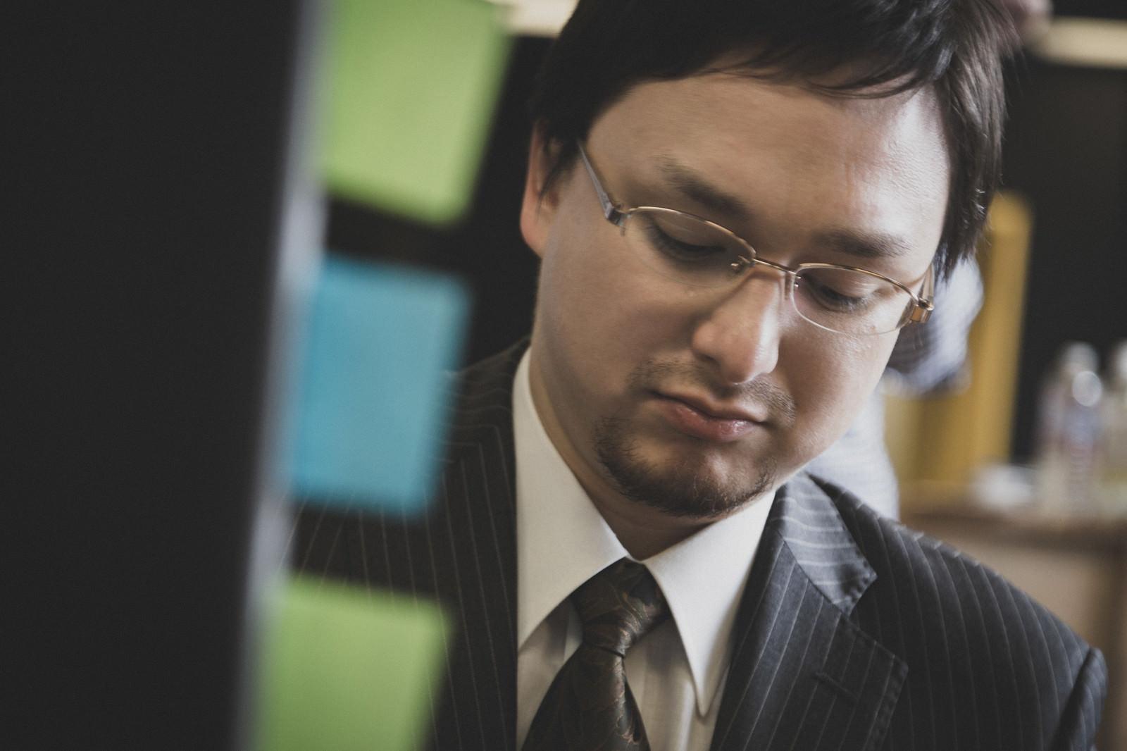 「勤務中に株の暴落を知った会社員投資家」の写真[モデル:Max_Ezaki]