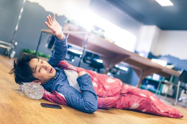早朝、連日の残業で寝袋姿の上司の写真