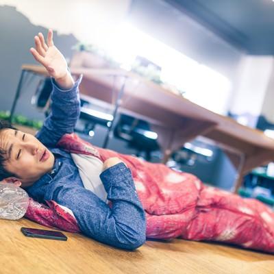 「早朝、連日の残業で寝袋姿の上司」の写真素材