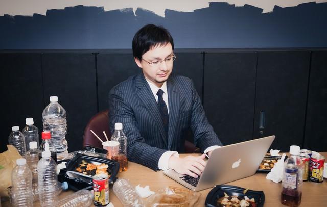 飲みかけの大量のペットボトルと食べかけのカップラーメンを放置して仕事する同僚の写真