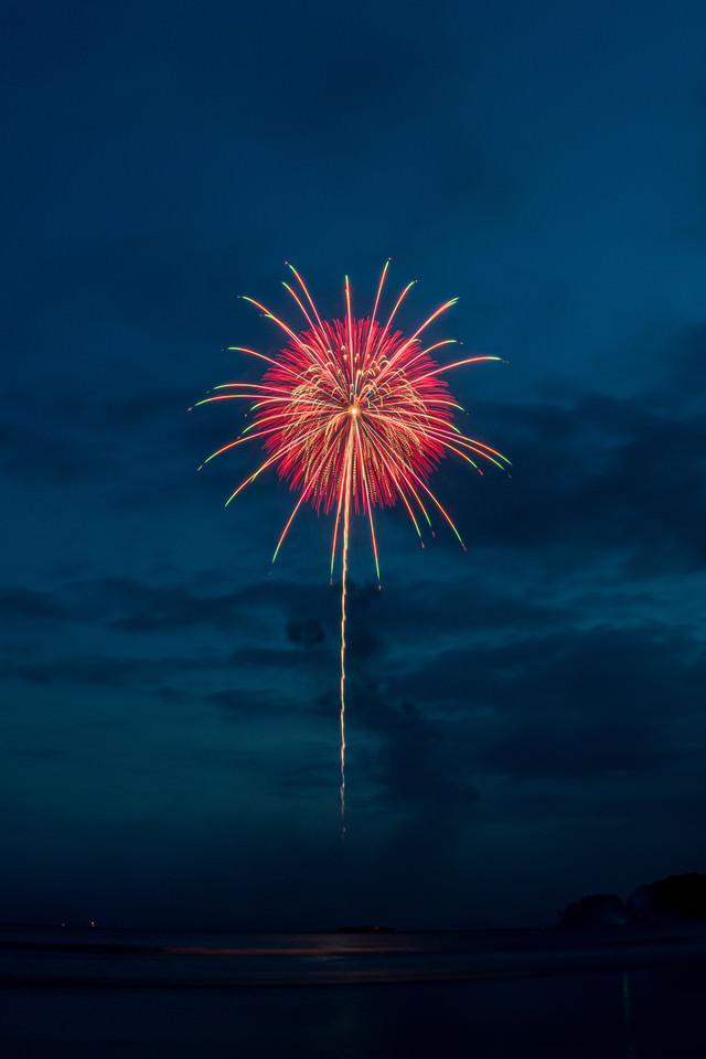 海上から打ち上がる花火の写真