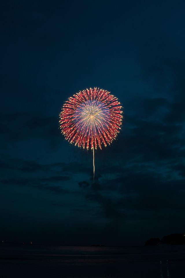 日が落ちてきた夜空に上がる花火の写真