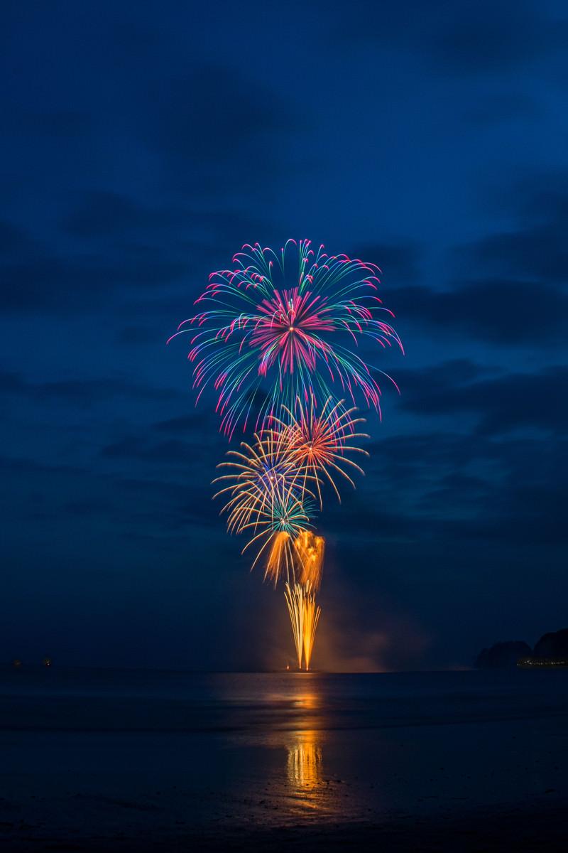 「日が落ちた夜空に打ち上がる花火」の写真