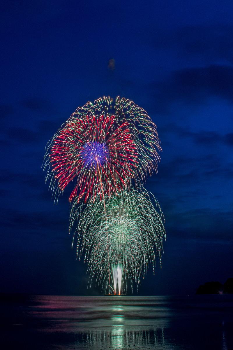「海上で打ち上げられるスターマイン花火」の写真