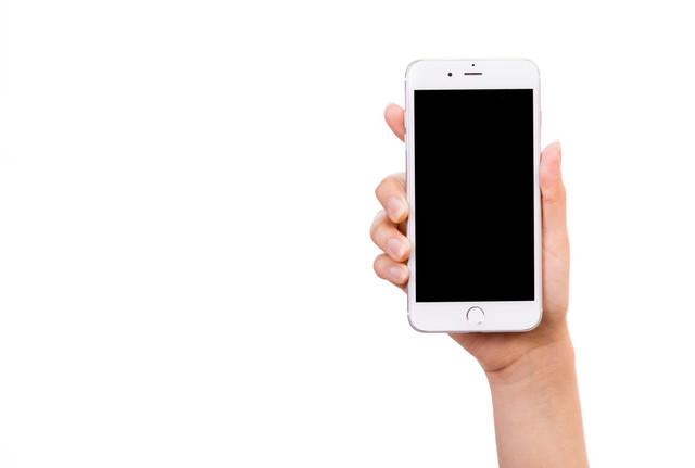 スマートフォンを手に持って画面を見せる(切り抜きしやすい)の写真