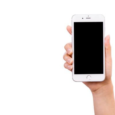 「スマートフォンを手に持って画面を見せる(切り抜きしやすい)」の写真素材