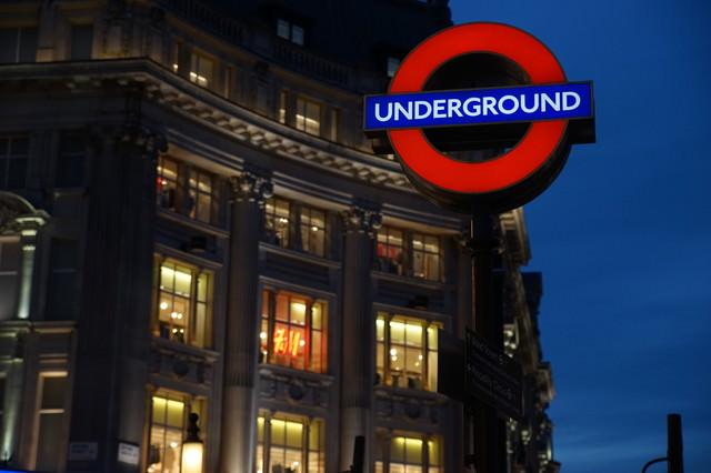 ロンドンの街並みと地下鉄の入口案内板の写真