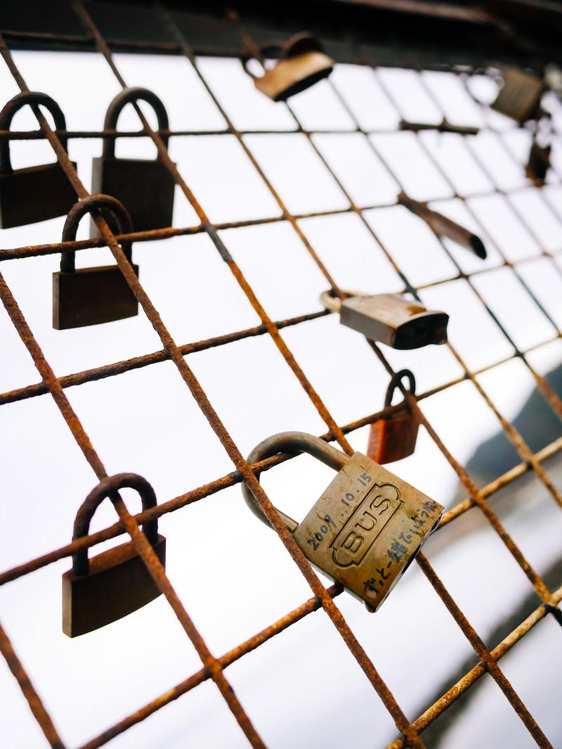 「金網に留まるメッセージ入りの南京錠」の写真