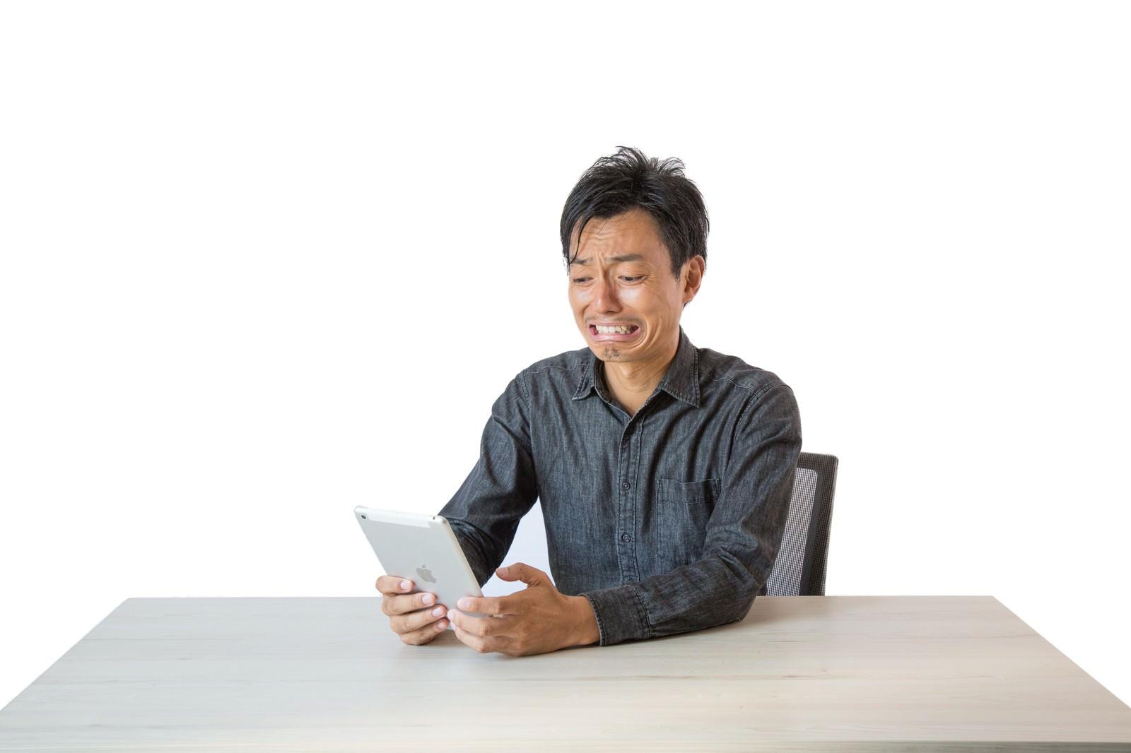 「電子書籍を読みながら涙する男性」の写真[モデル:藤沢篤]