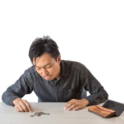 残りの生活費を計算する男性の写真