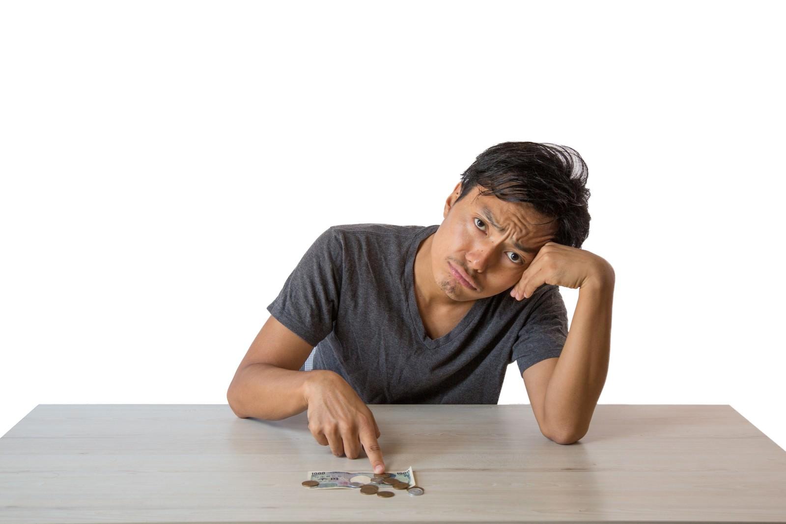 「月末までの生活費に頭を悩ます浪費癖のある男性」の写真[モデル:藤沢篤]