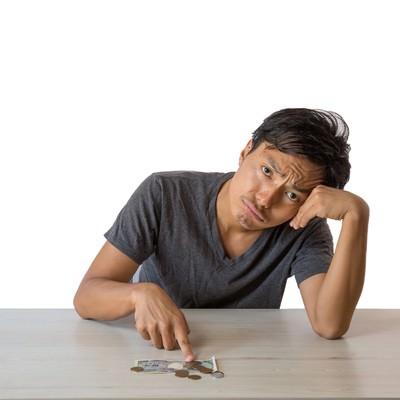 月末までの生活費に頭を悩ます浪費癖のある男性の写真