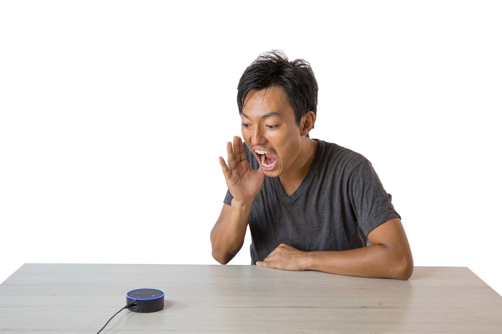 「スマートスピーカーに大声で話しかける男性」の写真[モデル:藤沢篤]