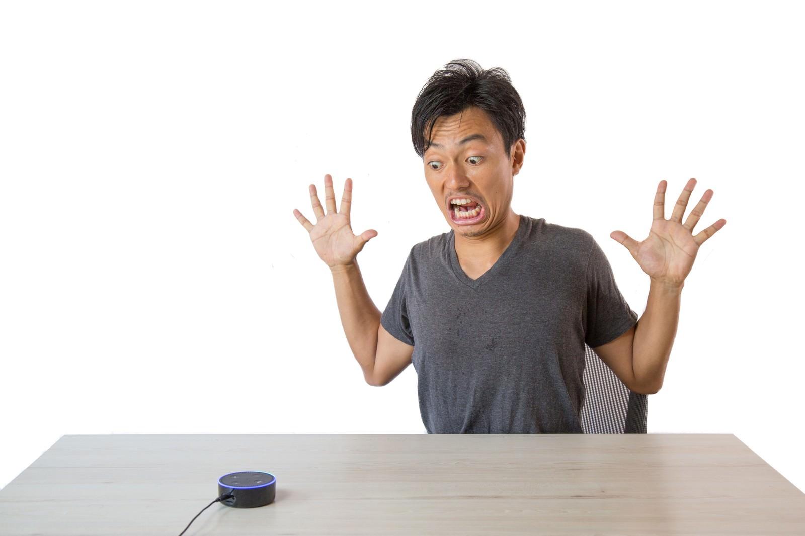 「スマートスピーカーのまさかの反応に驚く男性」の写真