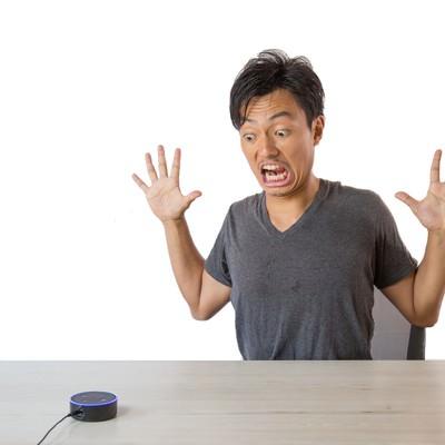 スマートスピーカーのまさかの反応に驚く男性の写真