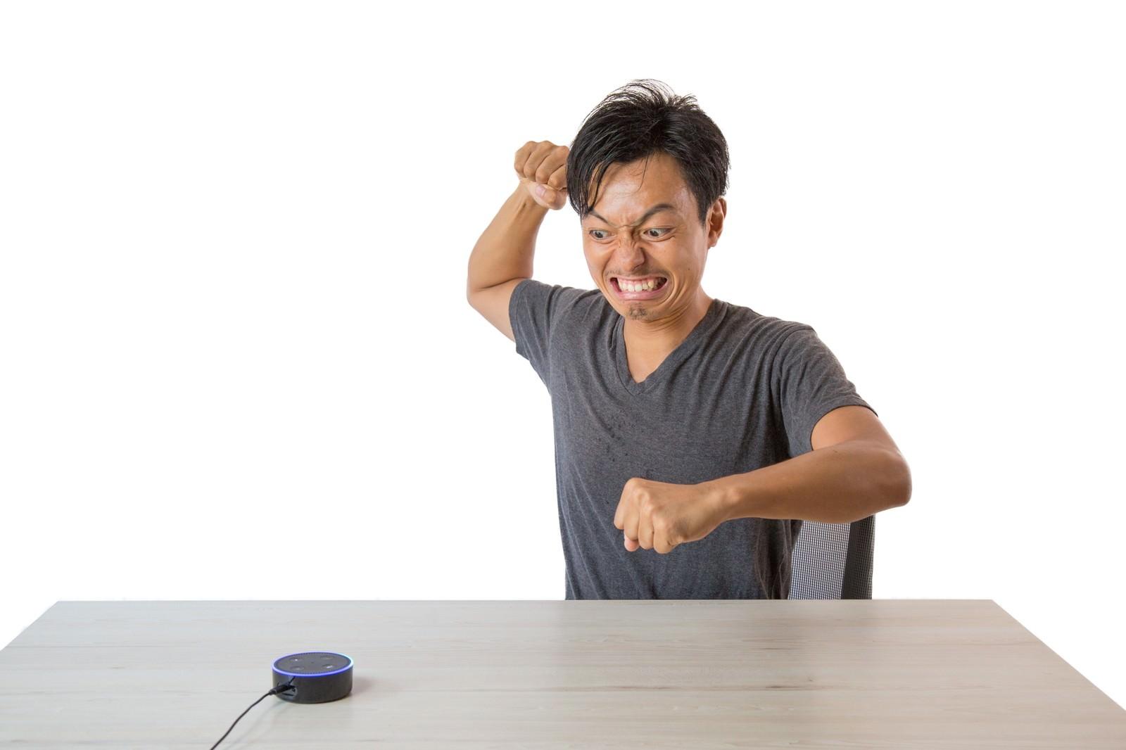 「音声アシストに認識されずスマートスピーカーに逆切れする男性」の写真[モデル:藤沢篤]