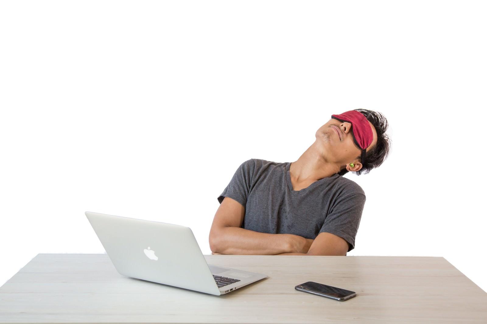 「アイマスクをして仮眠を取る男性」の写真[モデル:藤沢篤]