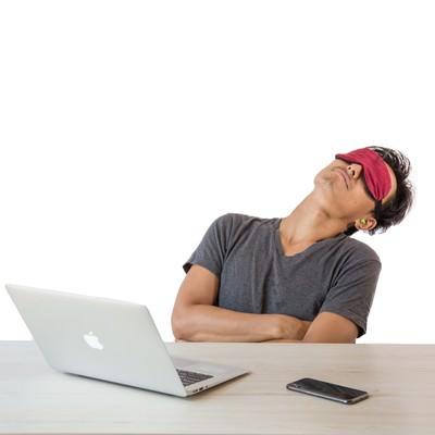 アイマスクをして仮眠を取る男性の写真