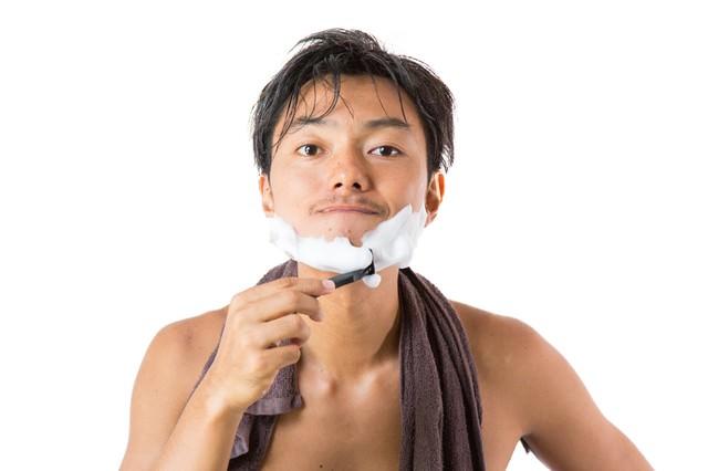 シェービングの泡でヒゲを剃る男性の写真